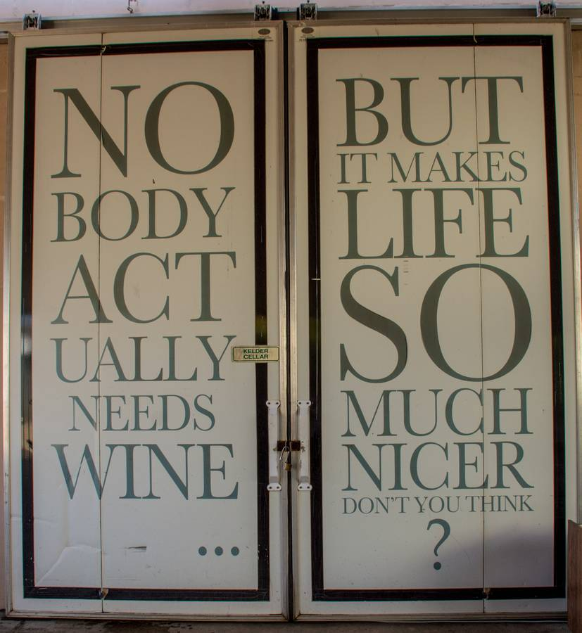Doors with slogan Nobody actually needs wine but it makes life so much nicer